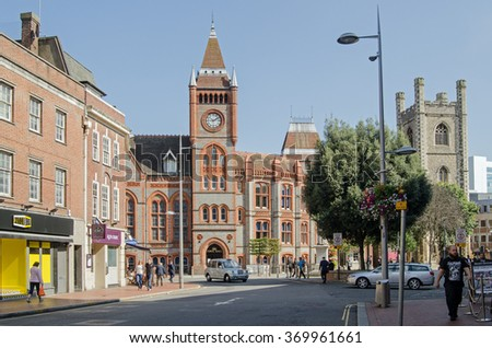 READING, BERKSHIRE - SEPTEMBER 10, 2015: Pedestrians in the centre of Reading in Berkshire on a sunny afternoon.  The old Town Hall - now a museum and cafes line the square with Saint Laurence church.