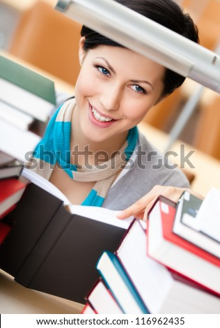Reading book female student surrounded with piles of books at the library. Learning process - stock photo