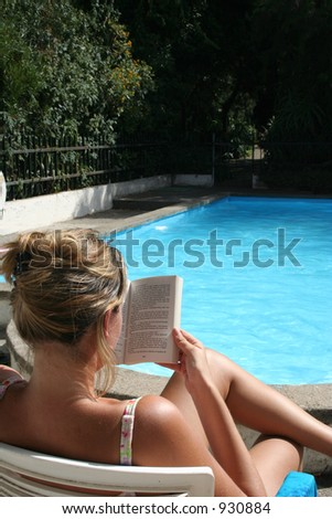 Reading by the pool - stock photo