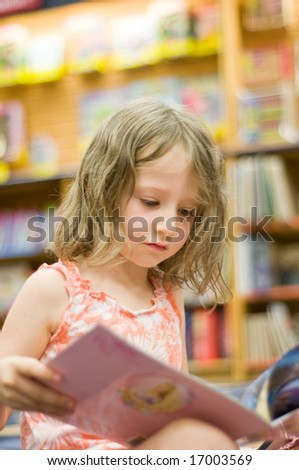 reading early - pretty four year old girl reads - stock photo