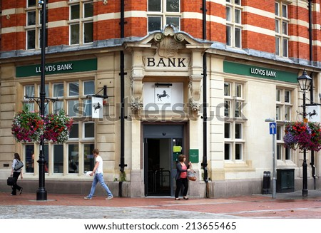 Reading, England - August 28th, 2014: A woman exits the Reading branch of Lloyds Bank as other people pass by. The UK Treasury owns 25% of Lloyds after a 20bn bailout during the 2008 financial crisis - stock photo