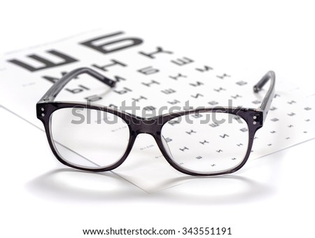 Reading eyeglasses and eye chart close-up on a light background - stock photo