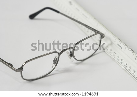 reading eyeglasses and ruler diagonally placed on table