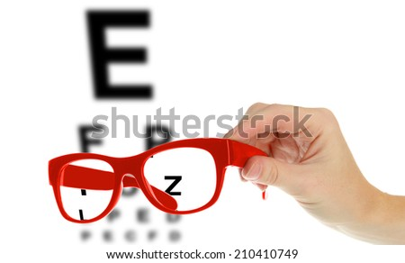 Reading eyeglasses in hand and eye chart - stock photo