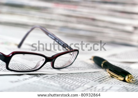 reading glasses and a ballpoint pen lie on a newspaper - stock photo