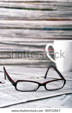 reading glasses and a coffee cup lie on a newspaper - stock photo