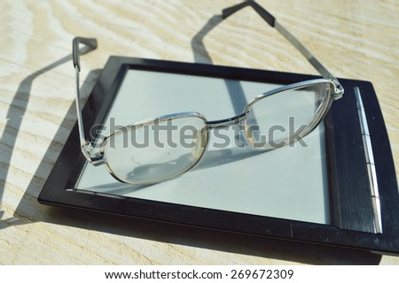 reading glasses and black e-book on a wooden table - stock photo