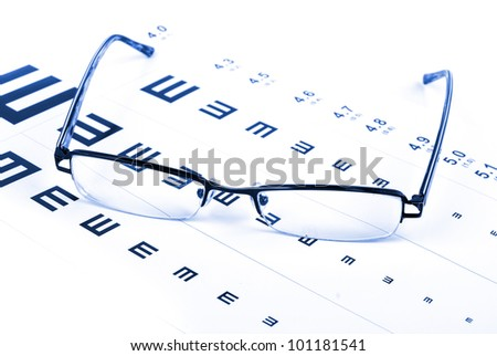 Reading glasses and eye chart - stock photo