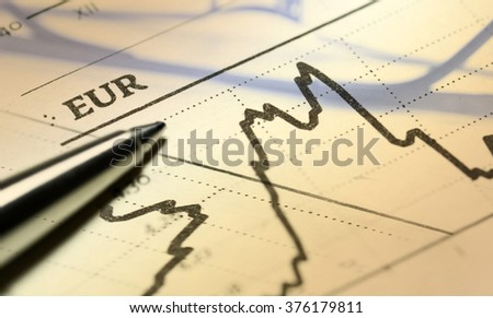 Reading glasses and pen over financial market graph. Business concept.  - stock photo