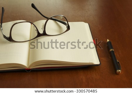 Reading glasses and schedule book and pen - stock photo