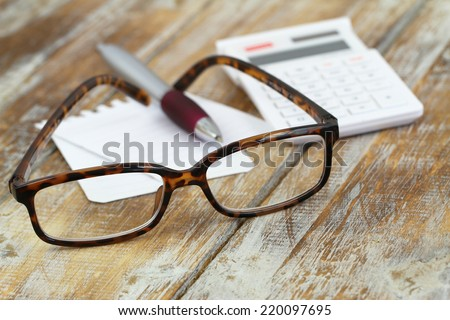 Reading glasses, calculator, pen and note paper on wooden surface