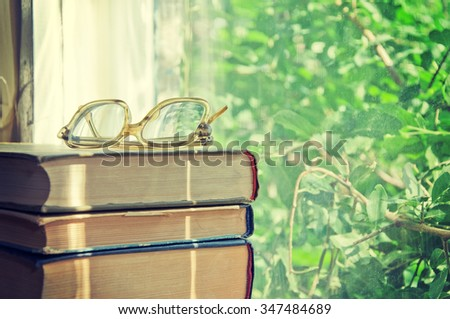 Reading glasses lay on a pile of books. Stock Photo. - stock photo