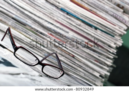 reading glasses lie before a big newspaper pile - stock photo