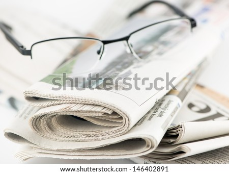 reading glasses lie on newspaper pile - stock photo