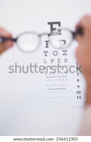 Reading glasses looking at eye test on white background