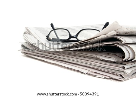 Reading glasses on stack of newspaper