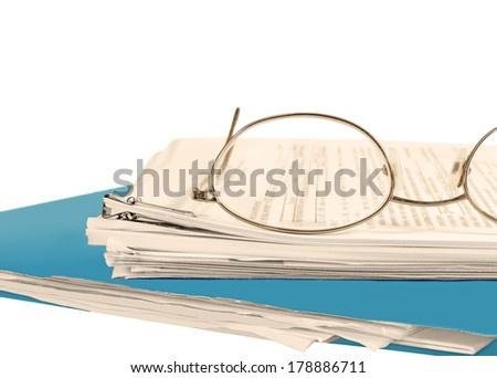 Reading glasses on stack of papers held together with bulldog paper clip.Blue folder on bottom. Blurred text. Horizontal, isolated with room for text, copy space. Office job stress concept.Sepia tint. - stock photo