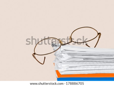 Reading glasses on stack of papers held together with bulldog paper clip. Blue, orange folders on bottom. Horizontal, isolated with room for text, copy space. Office job stress concept.  - stock photo