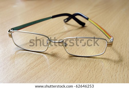 Reading glasses on the wooden background - stock photo