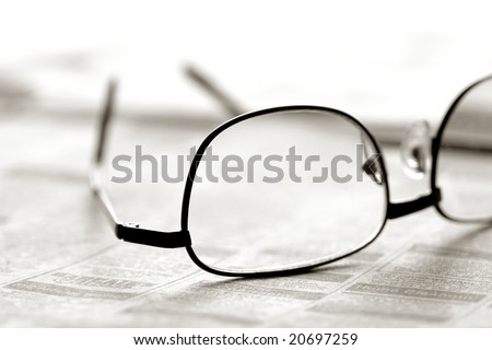 Reading glasses over classified section of a newspaper - stock photo
