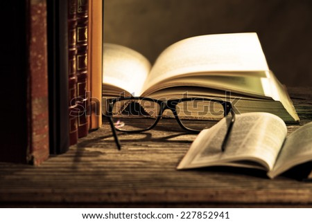 reading glasses with books on the table - stock photo