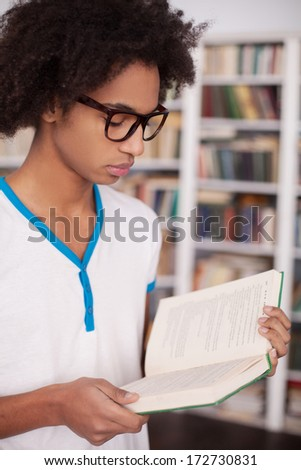 Reading his favorite book. Confident African teenager reading a book while standing at the library - stock photo