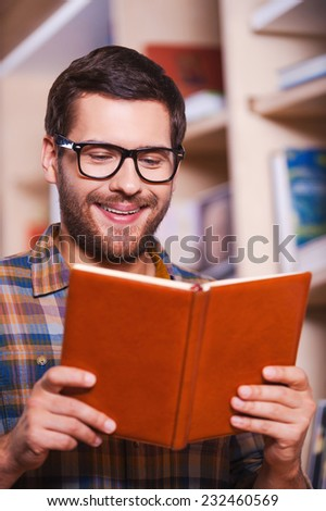 Reading his favorite book. Handsome young man reading book and smiling while standing in front of the bookshelf - stock photo