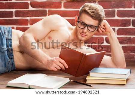 Reading his favorite book. Thoughtful young shirtless man reading book while lying on the floor at his apartment - stock photo