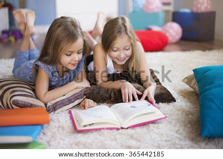 Reading interesting book with sister - stock photo