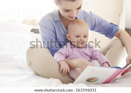 Reading interesting story with my mom  - stock photo