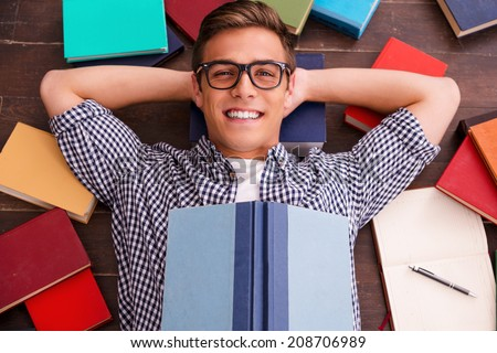 Reading is my hobby! Top view of happy young man holding hands behind head and smiling while lying on the hardwood floor with colorful books laying all around him  - stock photo