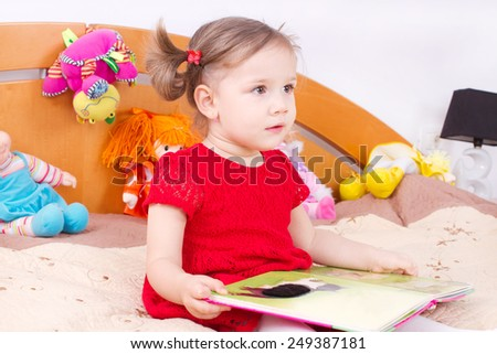 Reading little girl in bed - stock photo