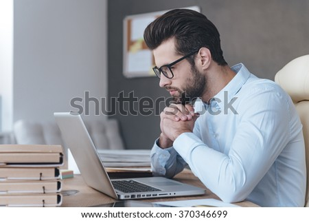 Reading new business plan. Side view of handsome young man wearing glasses working with laptop while sitting at his working place - stock photo