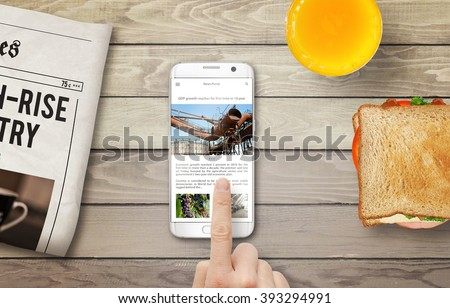 Reading news article on the phone during breakfast. Newspapers, juice and sandwich on the table with top view. - stock photo