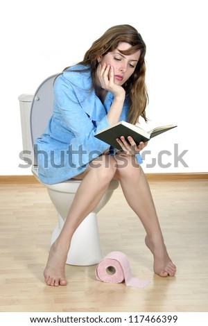 Reading on a toilet. Close up of the reading girl on a toilet. - stock photo