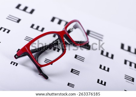 Reading red eyeglasses and eye chart close-up on a light background - stock photo