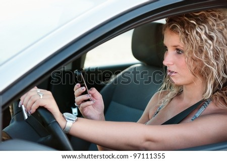 Reading SMS while driving car - stock photo