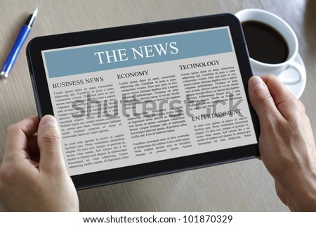 Reading the news on a digital tablet - stock photo