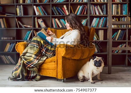 Beautiful Woman In Cozy Chair In Library With Her Funny Smart Dog Pug