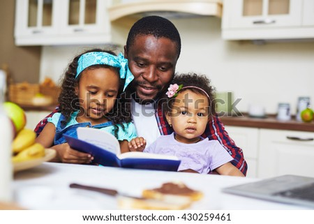 Reading with daughters - stock photo