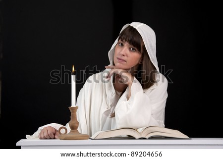 reading woman in white, with candle . On dark background