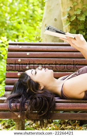 Reading woman laying in a park bench. - stock photo