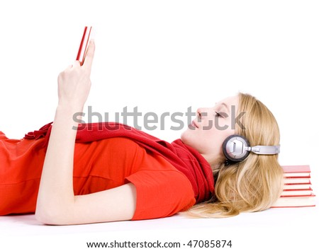 Reading young woman in headphones lying on heap of books - stock photo