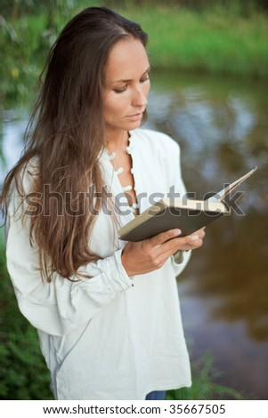 Reading young woman near the river - stock photo