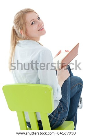 reading young woman sitting on the green, child's chair - stock photo