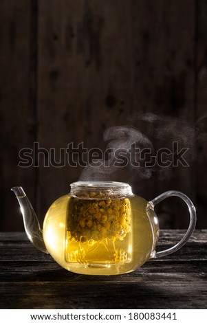 Ready and Hot Chamomile Tea in a Clear teapot on a Wood Table