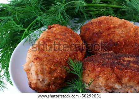 Ready cutlets are laid out on a white plate with a fennel branch.