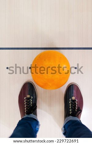 Ready for a game. Close-up of a bowling ball lying near human legs   - stock photo