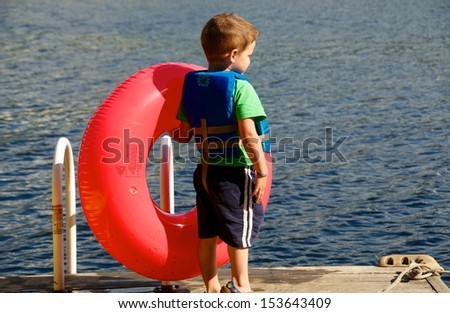Ready for a swim young boy holds a tube and has his life jacket on waiting on the dock - stock photo