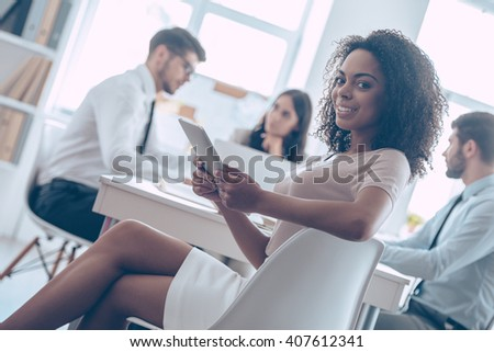 Ready for brainstorming. Beautiful cheerful African woman holding digital tablet and looking at camera with smile while sitting at the office table with her coworkers - stock photo